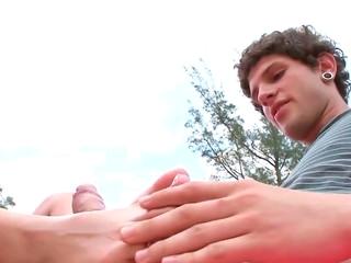 Skinny brunette AJ gives a footjob in a public